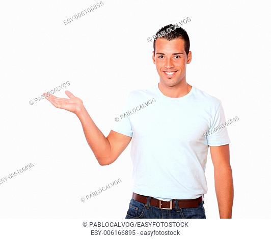 Portrait of a charismatic guy on white t-shirt holding out his right palm while standing and looking at you on isolated background - copyspace