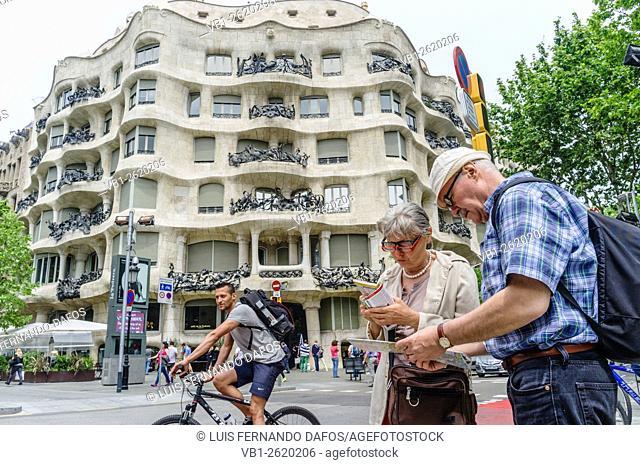Couple of older tourist checking a map opposite Casa Milà (known as La Pedrera) by Antoni Gaudí, at 92, Passeig de Gràcia, Barcelona, Spain