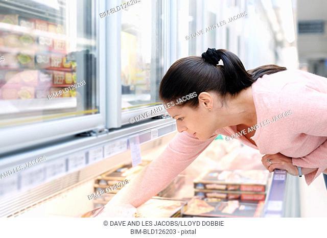 Hispanic woman looking through frozen food in supermarket