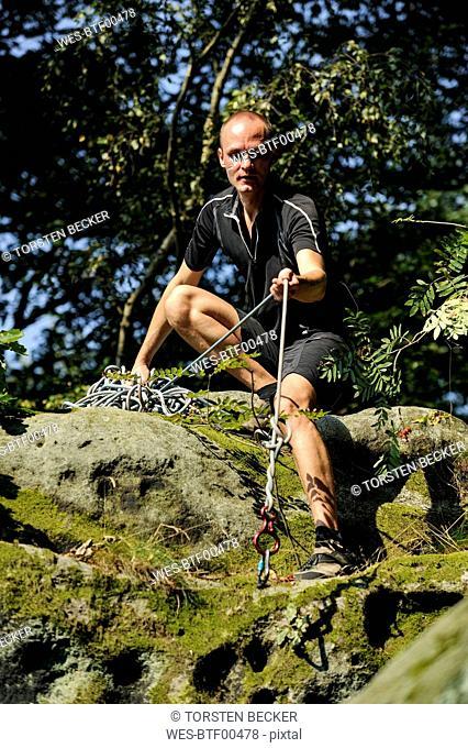 Climber crouching on a rock