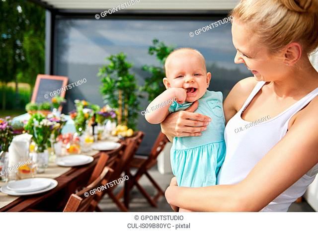 Young woman carrying baby daughter at family lunch by patio table