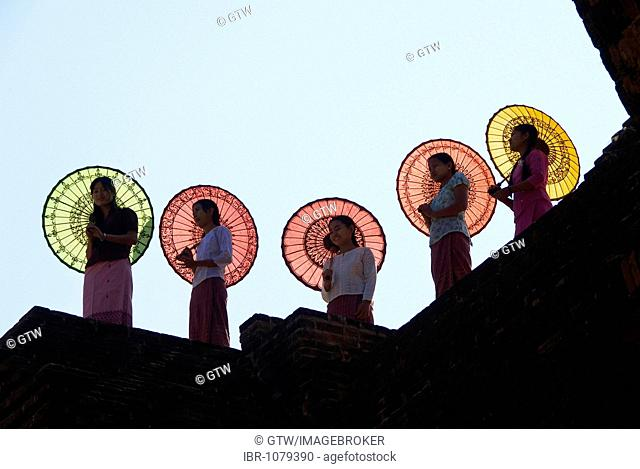 Young Burmese women with coloured parasols standing on a temple wall, Bagan, Myanmar