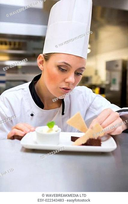 Smiling chef putting mint on the plate with cake in the kitchen