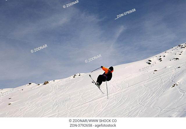 extreme freestyle ski jump with young man at mountain in snow park at winter season
