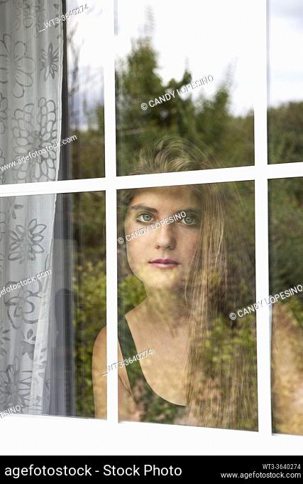 Portrait of teenage girl behind the window, reflections of vegetation in the glass