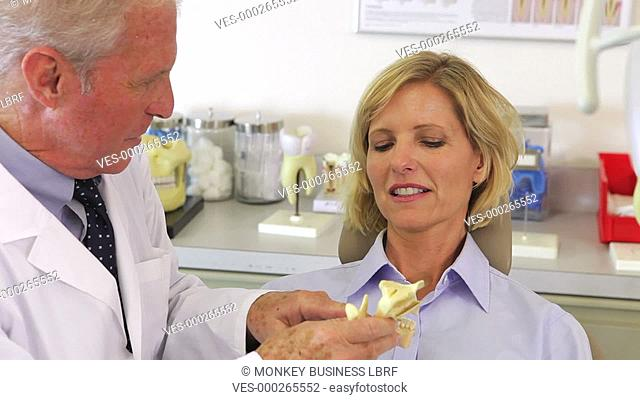 Dentist showing female patient model of human jaw and discussing dental problems. Shot on Canon 5d Mk2 with a frame rate of 30fps