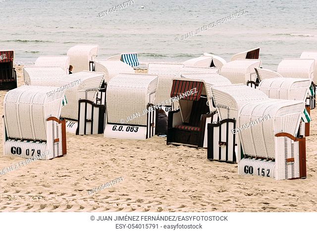 Hooded beach chairs in Baltic sea beach a cloudy day of Summer. Sellin, Rugen Island. Germany