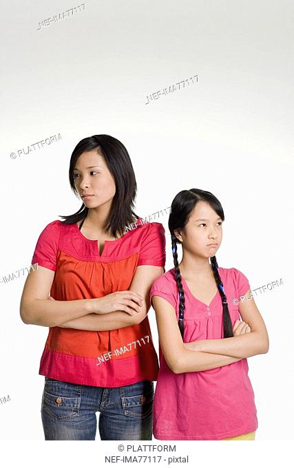 Woman and girl standing side by side