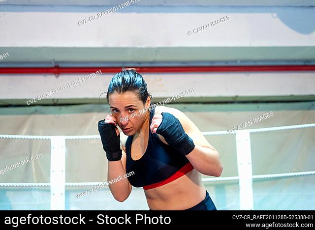 Female boxer ready to kick with black boxing bandage on hands in gym