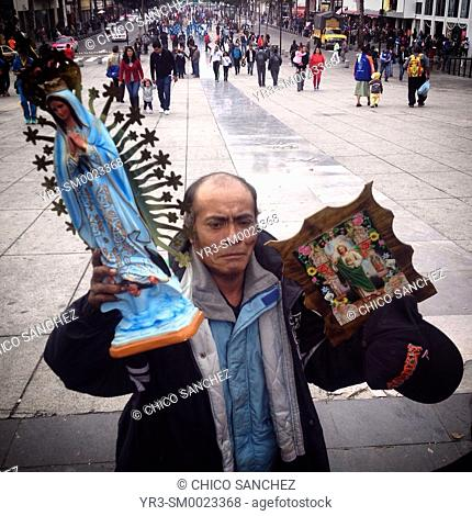 A pilgrim holds images of the Virgin of Guadalupe and Saint Jude Thaddeus during the annual pilgrimage to the Our Lady of Guadalupe basilica in Mexico City