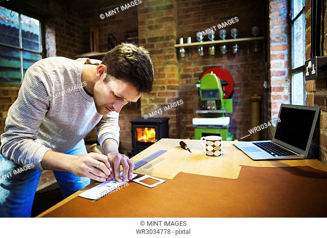 A craftsman using an awl and a ruler to measure and mark a small piece of leather. Workbench with a mug, hand tools and a laptop