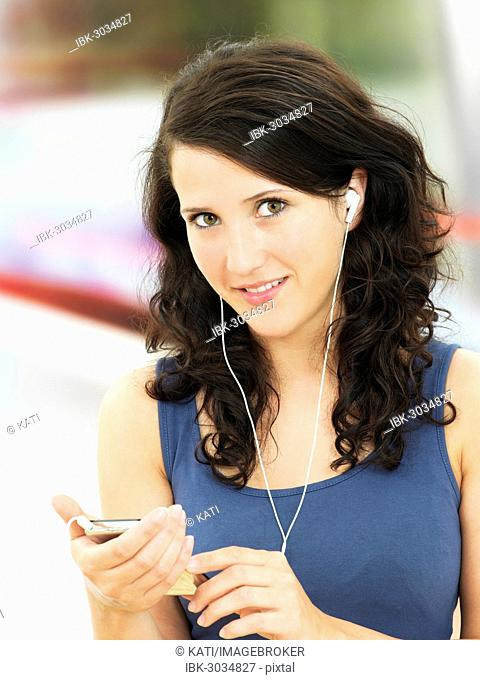 Young woman listening to music at a subway station