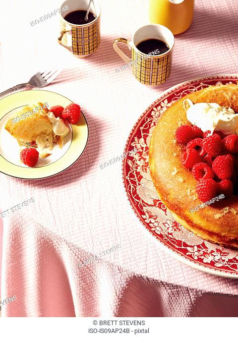 Overhead view of savarin cake with raspberries and cream