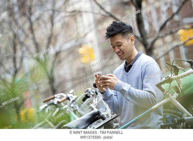 City life in spring. A man in a blue sweater by a row of parked bicycles. Checking his messages on a smart phone