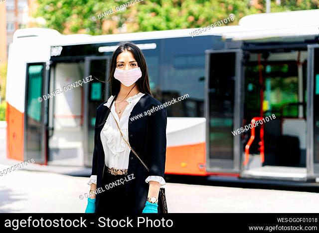 Portrait of young woman wearing protective mask and gloves waiting at bus stop, Spain