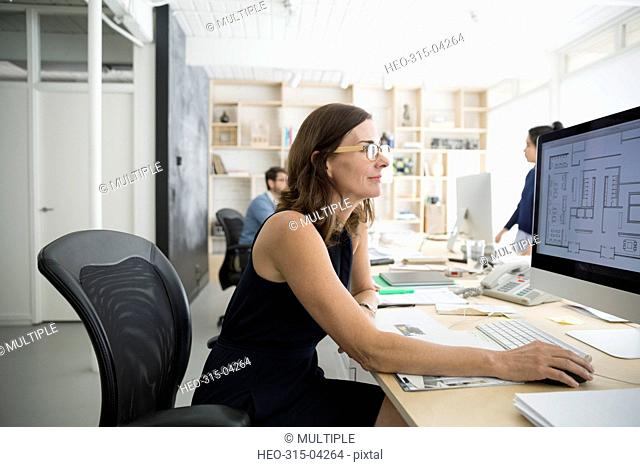 Female architect drafting blueprint on computer in office