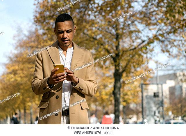 Portrait of businessman looking at cell phone in autumn