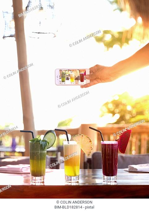 Pacific Islander woman photographing juices on counter