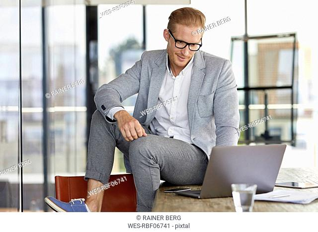 Smiling businessman sitting on desk in office using laptop