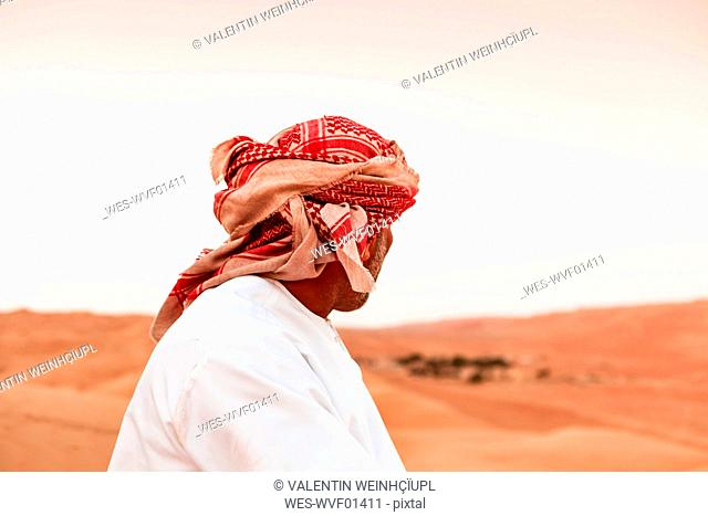 Bedouin in National dress standing in the desert, rear view, Wahiba Sands, Oman