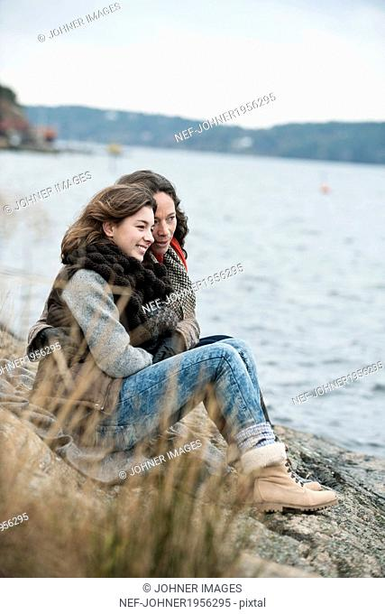 Mother and teenage daughter sitting at water