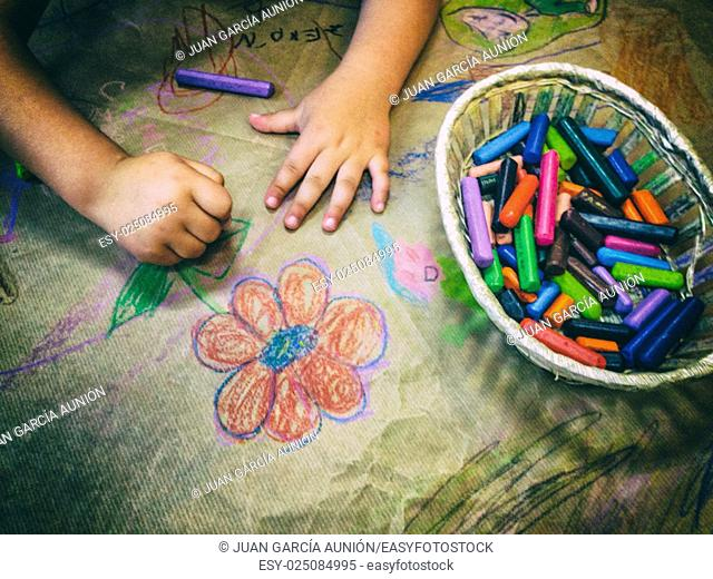 Child drawing with a basket of wax crayons over craft wrapping paper. High angle view
