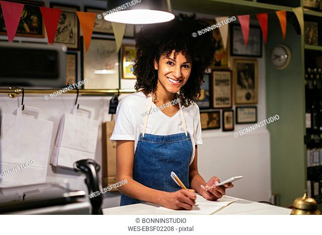 Portrait of smiling woman with cell phone and notebook in a store