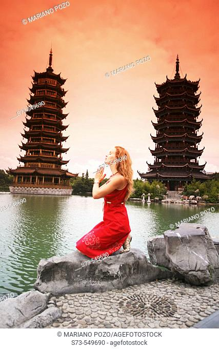 Woman praying next to the twin pagodas of Riming Shuang Ta. Guilin. China