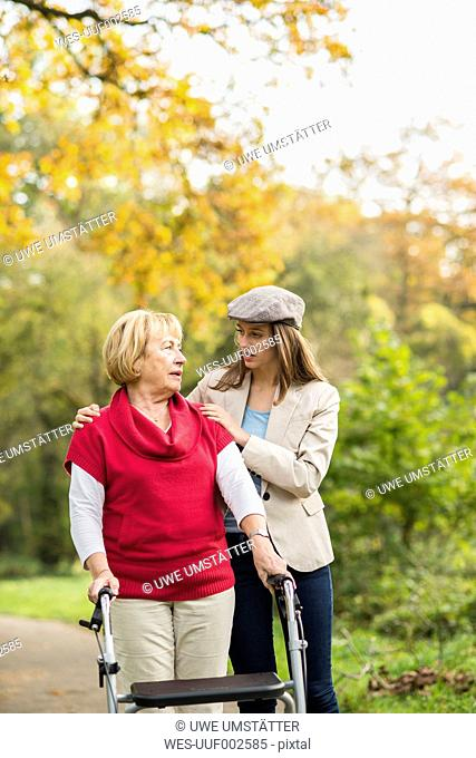 Senior woman and her caring adult granddaughter walking together in autumnal park