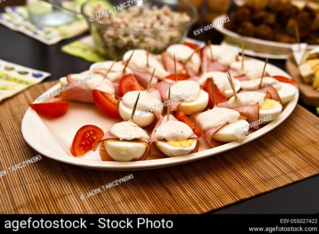 eggs with mayonnaise, ham and tomato on the plate
