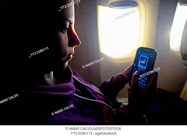 Young woman using phone on flight
