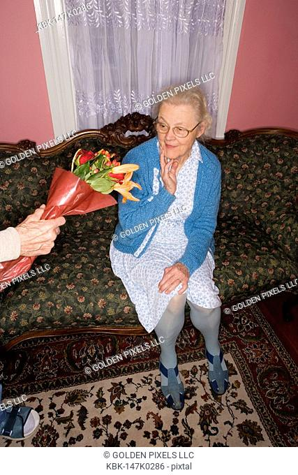 Surprised and happy senior woman sitting on the sofa handed bouquet of flowers