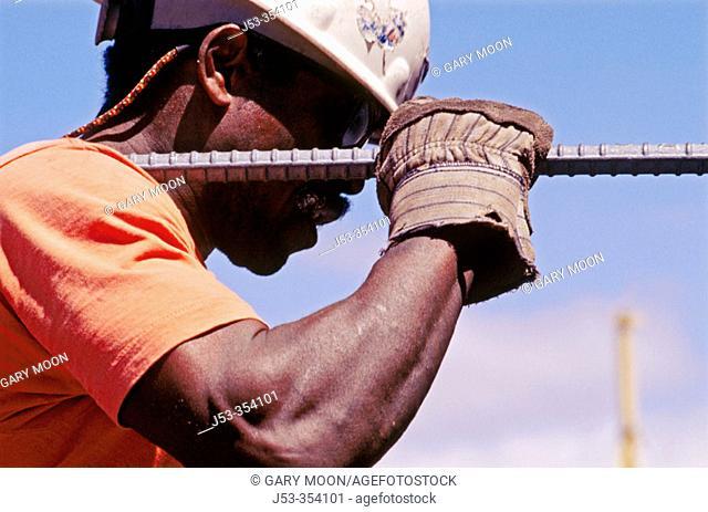 Ironworker carrying long rebar. I-880 Cypress project. Oaklnad, California. USA