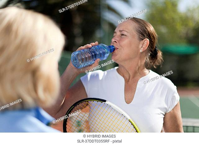 Older woman having water on tennis court