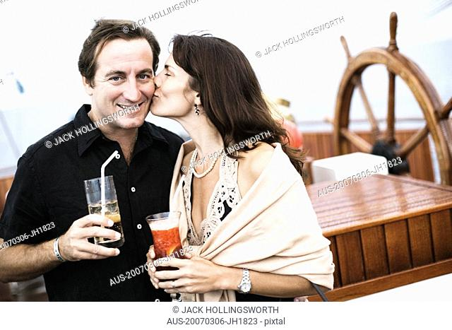 Mid adult woman kissing a mid adult man on a sailing ship