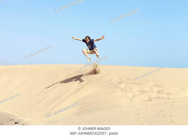 Young man jumping on sand dune