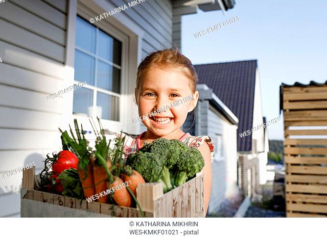 Portrait of happy little girl with wooden box of organic vegetables