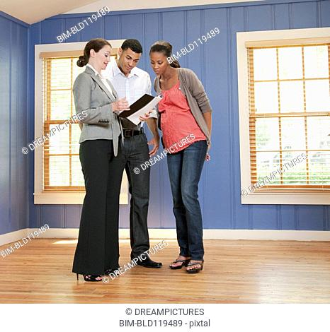 Couple talking with realtor in empty house