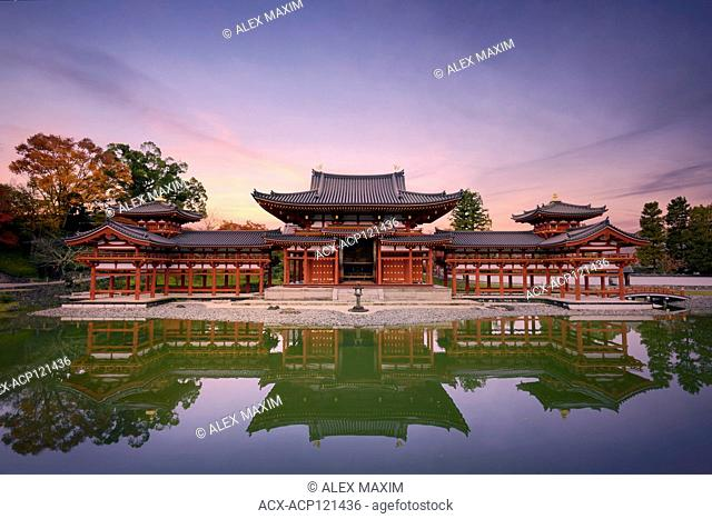 Beautiful tranquil sunset scenery of the Phoenix or Amida Hall of Byodoin, Byodo-in Japanese Buddhist temple reflecting in the clear calm water of Jodoshiki...