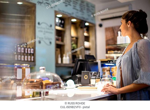 Young woman waiting at cafe counter