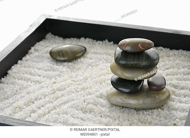 Stacked polished rocks in a miniature Zen rock garden sandbox