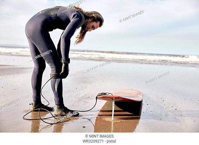 Man preparing to surf on a sandy beach in a wetsuit