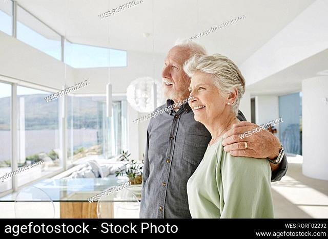 Happy senior couple in luxury beach house looking out of window