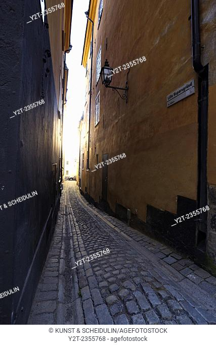 Bright sunlight shines at the end of a narrow alley in Gamla Stan, the old town of Stockholm, Sweden
