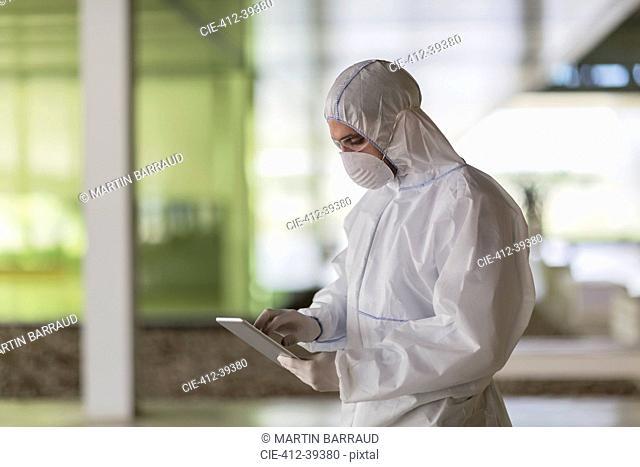 Scientist in clean suit using digital tablet
