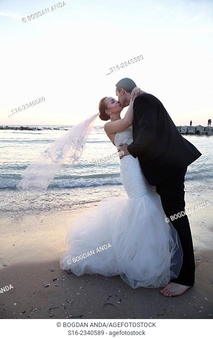 Bride and groom kissing on the beach on sunrise/ sunset background