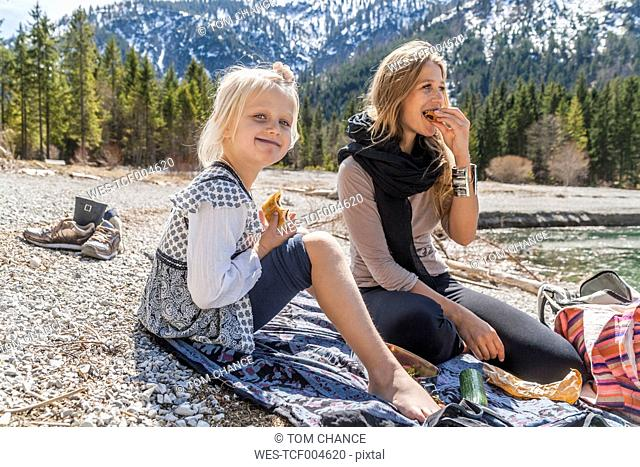 Austria, Tyrol, Lake Plansee, mother and daughter resting at lakeshore
