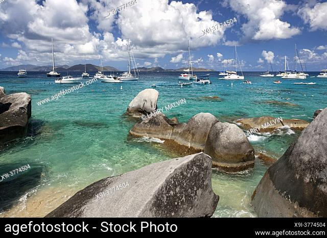 Boulders dot the shoreline of the Baths with boats moored in the distance at the Baths on Virgin Gorda in the British Virgin Islands