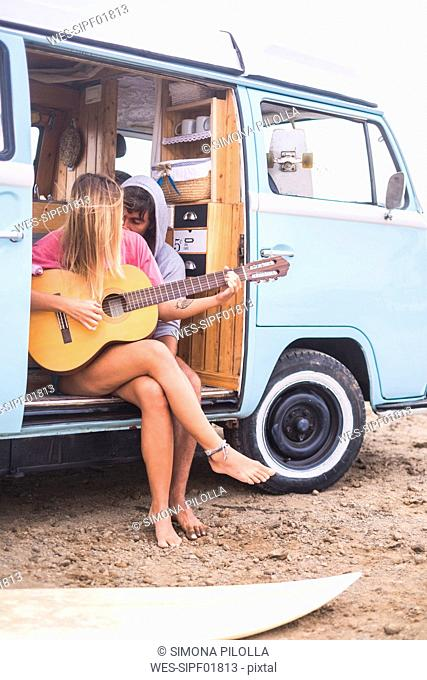 Young couple with guitar and surfboard in van on the beach