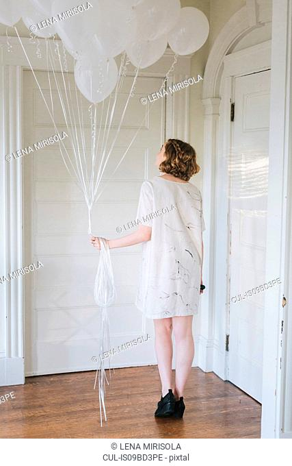Woman in apartment holding bunch of balloons, rear view